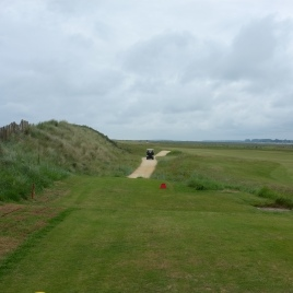 The view from the 1st tee. Note the proximity of the out-of-bounds fence (and beach immediately beyond) to the left, and the 18th green to the right. The ideal line from the tee (and shortest route home) is down the left-hand side, following the alignment of the cart path.