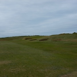 The view from the 16th fairway. Note the three bunkers, starting with two on the right-hand side of the fairway and a third set into the bank to the front left of the green. The staggered arrangement of these bunkers, set against the left to right dog-leg shape of the hole gives an advantage to those who can safely drive down the right-hand side of the fairway and avoid the first two of these hazards. The further left you go with your tee shot the more the bunker guarding the left half of the green comes into play.