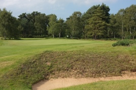 The view of the 9th green from the right-hand side of the fairway, showing one of two bunkers that flank the approach to the putting surface.