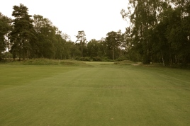 The view from the 16th fairway. The small mound extending into the fairway from the left-hand side obscures your view of the putting surface, and is home to the hole's lone bunker. The best line from the tee is therefore down the right-hand side, which opens up a view of the green sited just beyond the mound.