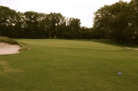 The view of the 15th green from front left showing the steep false front that feeds short approaches into the adjacent greenside bunker on the right.