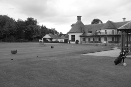The view looking to the south-west across the 1st tee, with the practice putting green just beyond the tee and the clubhouse to the right.
