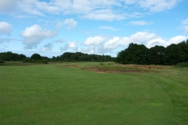 The view from the start of the 7th fairway, showing the cluster of four fairway bunkers that sit in the right-hand rough, on the inside of the dog-leg.