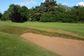 The view of the back portion of the 9th green from the left-hand side, over the bunker which guards this side of the putting surface.