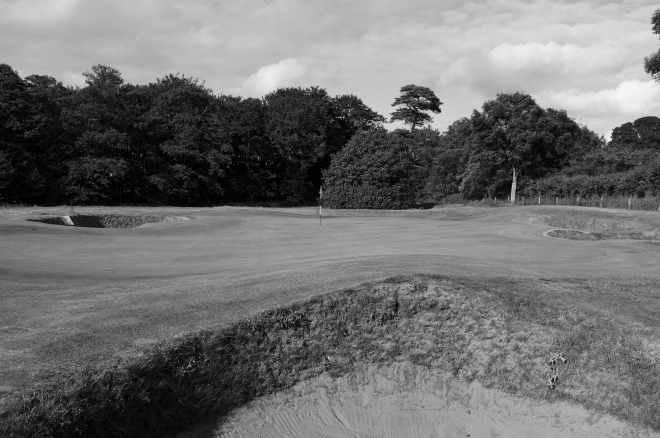 The view of the undulating 10th green from front right, over one of six bunkers that encircle the putting surface.